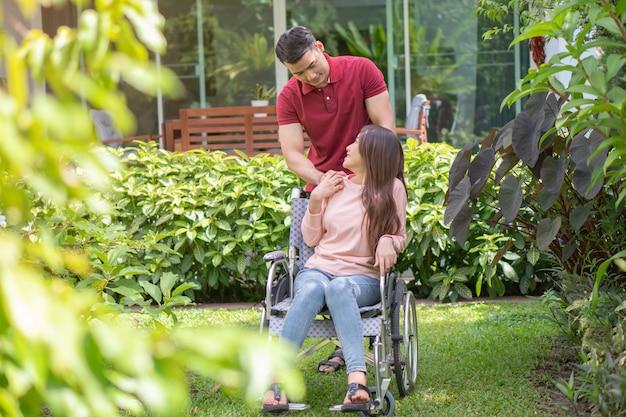 Mulher asiática na cadeira de rodas e sorrindo com o marido.