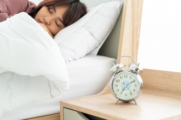 Mulher asiática na cama e acordar de manhã