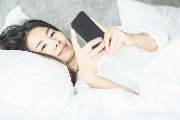Mulher asiática na cama usando telefone inteligente