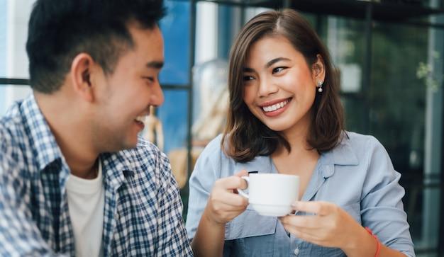 Mulher asiática na camisa azul no café, bebendo café e conversando com o namorado sorriso e cara feliz