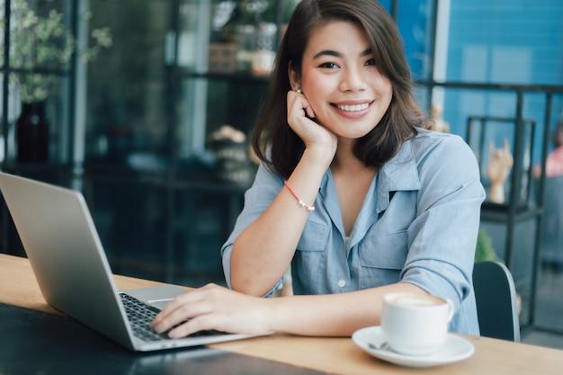 Mulher asiática na camisa azul no café, bebendo café e usando o computador portátil trabalhando marketing on-line de negócios