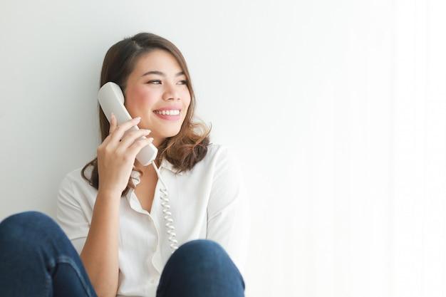 Mulher asiática na camisa branca usando telefone vintage falando, na sala de estar