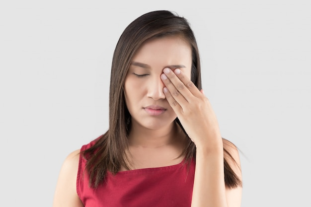 Mulher asiática na camisa vermelha tem dor nos olhos em um fundo cinza