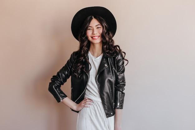 Mulher asiática na jaqueta de couro em pé com a mão no quadril. foto de estúdio de uma mulher chinesa sorridente com chapéu isolado no fundo bege.