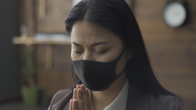 Mulher asiática na máscara orando em isolamento durante epidemia