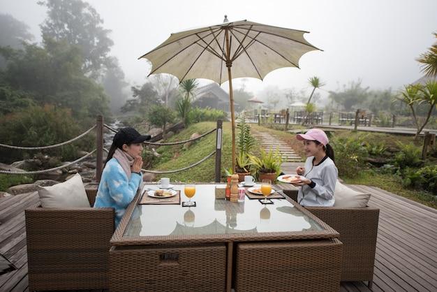 Mulher asiática na tabela de café da manhã da manhã.