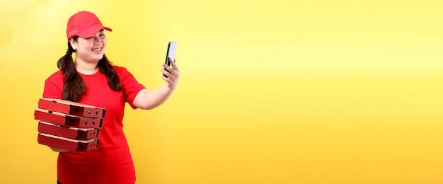 Mulher asiática na tampa vermelha, dando comida italiana pedir pizza italiana em caixas de papelão isolado segurando o telefone móvel com tela vazia branca em branco.