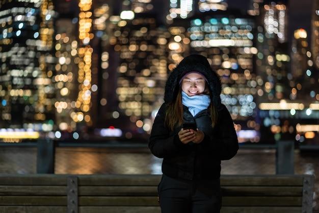 Mulher asiática no inverno terno usando telefone móvel esperto com sorriso ação sobre a foto turva bokeh