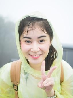 Mulher asiática no rainwear amarelo olhando para a câmera.