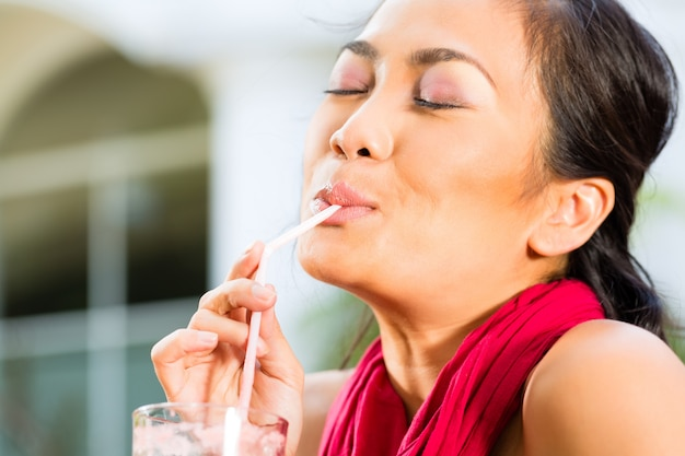 Mulher asiática no restaurante bebendo