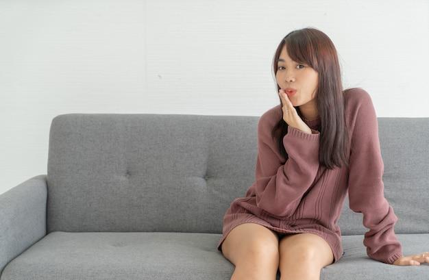 Mulher asiática no sofá na sala de estar com espaço de cópia