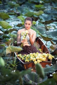 Mulher asiática no vestido tradicional rural tailandesa sentado no barco no jardim de lótus na manhã