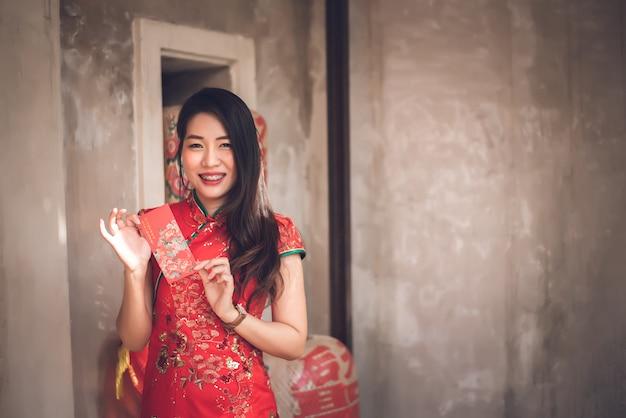 Mulher asiática no vestido vermelho tradicional de cheongsam no ano novo chinês