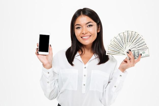 Mulher asiática nova alegre que guarda o dinheiro que mostra a exposição do telefone.
