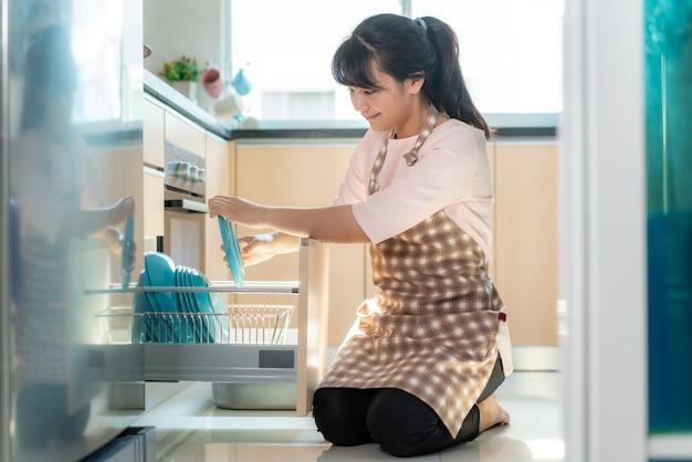 Mulher asiática nova atrativa que carrega a máquina de lavar louça em armários na cozinha ao fazer a limpeza em casa durante ficar em casa usando o tempo livre sobre sua rotina diária de limpeza.