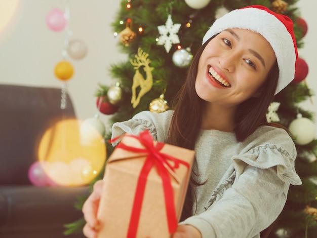 Mulher asiática nova atrativa que guarda uma caixa de presente, conceito do natal feliz.