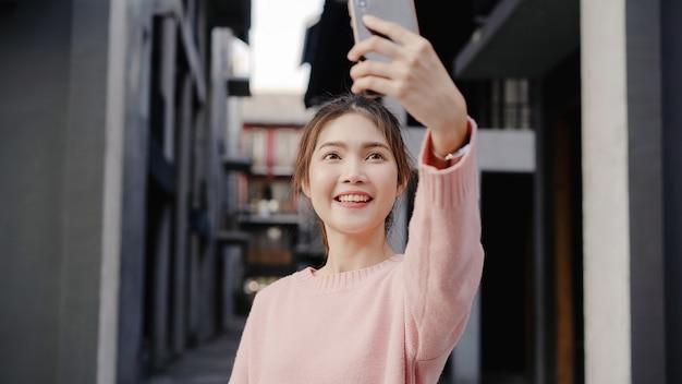 Mulher asiática nova bonita alegre do blogger do mochileiro que usa o smartphone que toma o selfie ao viajar no bairro chinês no pequim, china.