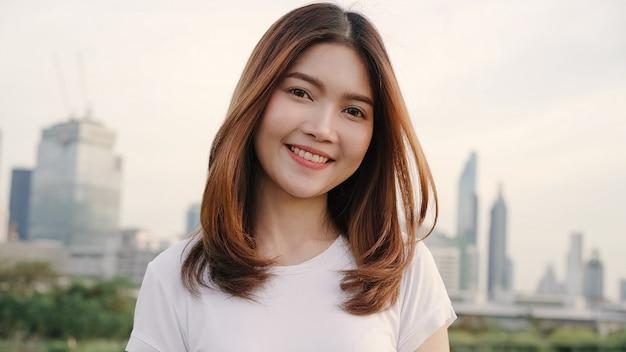 Mulher asiática nova bonita alegre que sente o sorriso feliz à câmera ao viajar na rua na cidade do centro.
