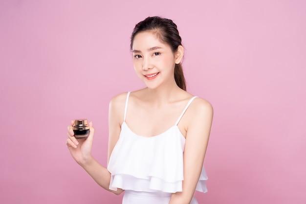 Mulher asiática nova bonita com a pele branca fresca limpa que guarda a mão facial do produto um do creme do tratamento com sorriso.