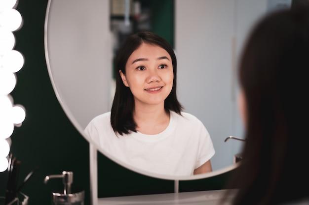 Mulher asiática nova bonita da afiliação étnica que olha-se no espelho no vestuario.