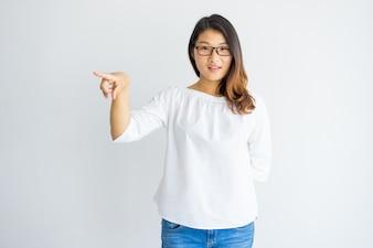 Mulher asiática nova bonita de sorriso que pede e que aponta de lado.