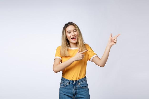 Mulher asiática nova bonita que aponta seu dedo acima com expressão alegre