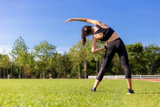 Mulher asiática nova bonita que estica durante seu exercício da manhã no campo de grama de uma pista de atletismo