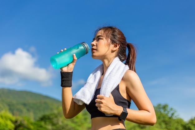 Mulher asiática nova bonita que exercita na manhã em uma pista de atletismo, tomando um descanso para beber a água