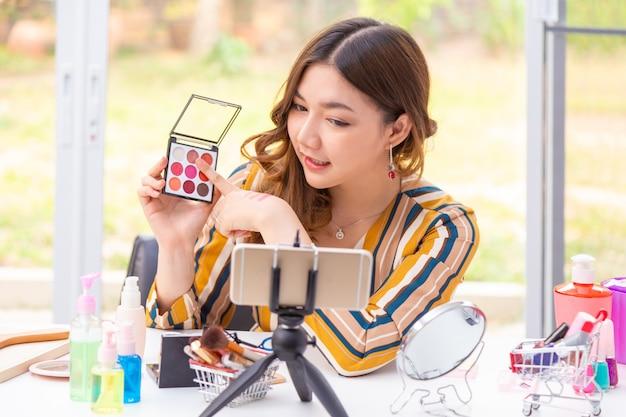 Mulher asiática nova bonita que faz a revisão em linha do produto em casa