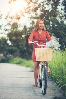 Mulher asiática nova bonita que monta uma bicicleta em um parque