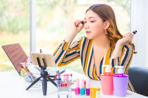 Mulher asiática nova bonita que põe a compõe durante sua revisão em linha do produto de beleza em casa