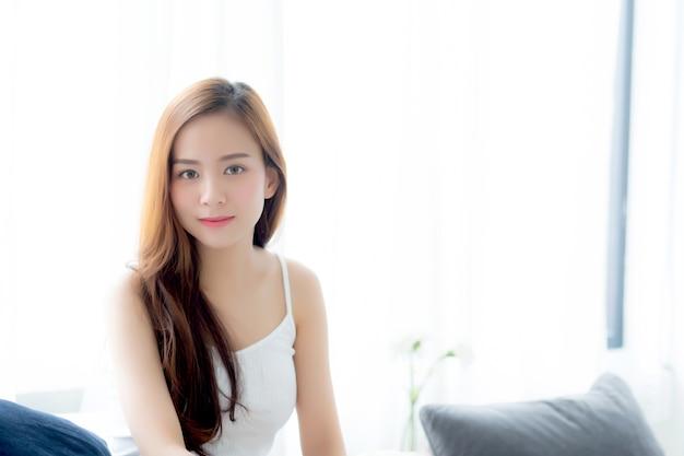 Mulher asiática nova bonita que senta a janela e sorriso quando acordar com nascer do sol.