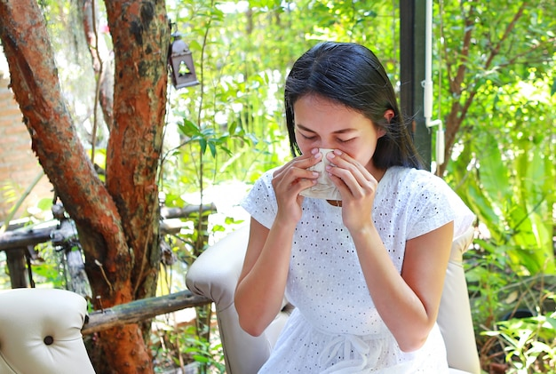 Mulher asiática nova bonita que senta-se no café usando um tecido