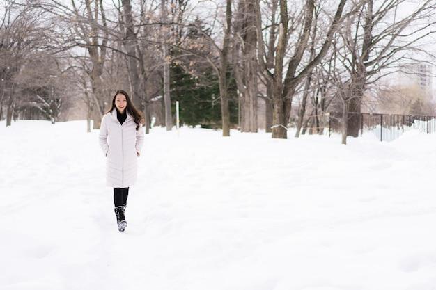 Mulher asiática nova bonita que sorri feliz para o curso na estação do inverno da neve