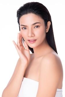 Mulher asiática nova bonita que toca no sorriso macio da bochecha com pele limpa e fresca felicidade e alegre, isolado no branco, beleza e cosméticos
