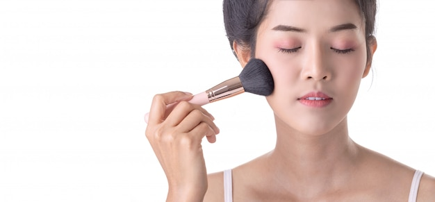 Mulher asiática nova bonita que usa a escova e o cosmético macios no próprio rosto.