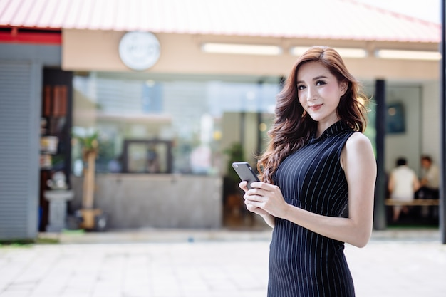 Mulher asiática nova bonita que usa o smartphone.