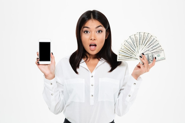 Mulher asiática nova chocada que guarda o dinheiro que mostra a exposição do telefone.