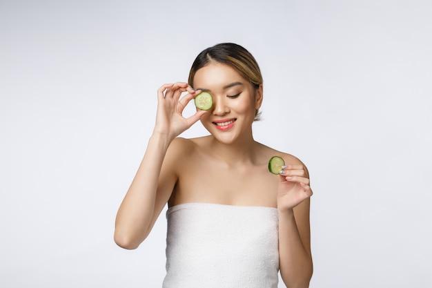 Mulher asiática nova com fatia do pepino em suas mãos isoladas no fundo branco.