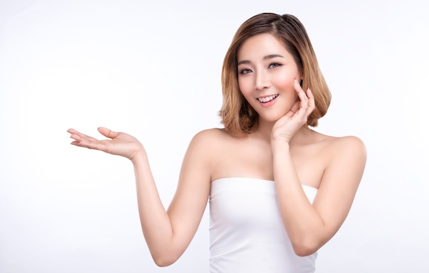 Mulher asiática nova da beleza que mostra a mão para o produto no branco.