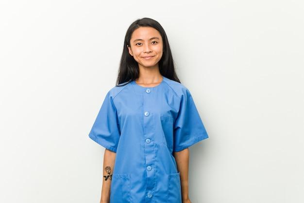 Mulher asiática nova da enfermeira feliz, sorrindo e alegre.