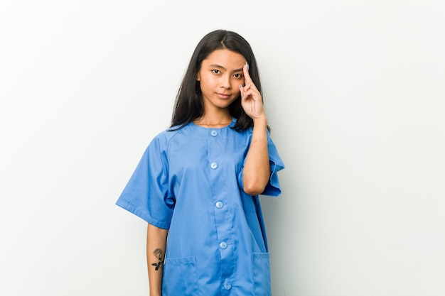Mulher asiática nova da enfermeira que aponta o templo com o dedo, pensando, focalizado em uma tarefa.