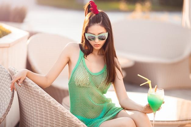 Mulher asiática nova da forma que bebe o cocktail em um bar da praia.