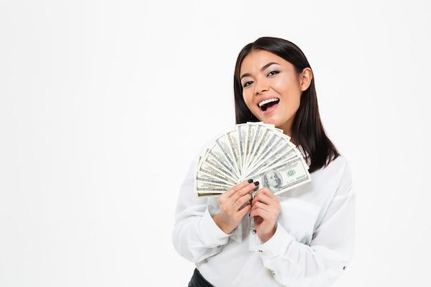 Mulher asiática nova de sorriso que guarda o dinheiro.