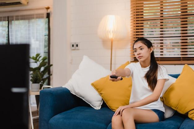 Mulher asiática nova do adolescente que olha a tevê em casa, fêmea que sente o encontro feliz no sofá na sala de visitas.