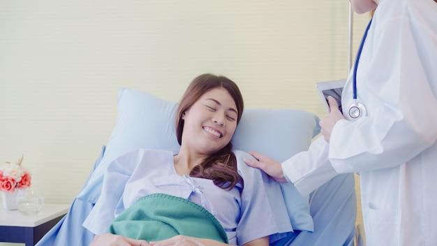 Mulher asiática nova do doutor que fala e que guarda a mão para o paciente das mulheres na cama doente.