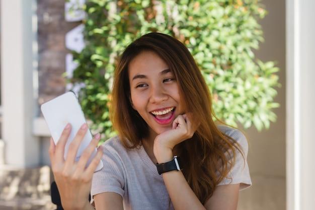 Mulher asiática nova feliz bonita atrativa que toma um selfie usando um telefone esperto no café