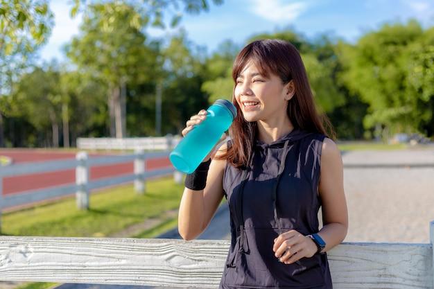 Mulher asiática nova feliz bonita que bebe sua água na manhã em uma pista de atletismo antes de começar seu exercício