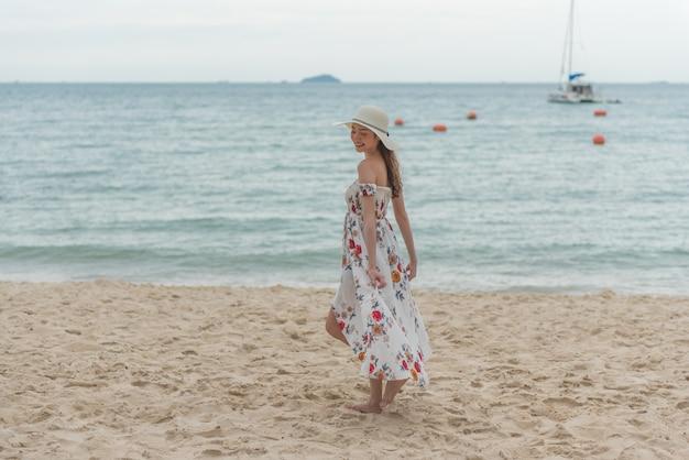 Mulher asiática nova feliz com chapéu que anda e que relaxa na praia da areia com felicidade.