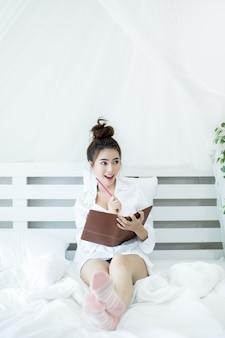 Mulher asiática nova feliz do estilo de vida que aprecia o encontro no livro de leitura da cama em casa.